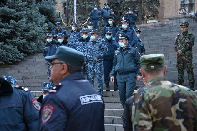 Armenian police officers guard the parliament building after protest against the country's agreement...