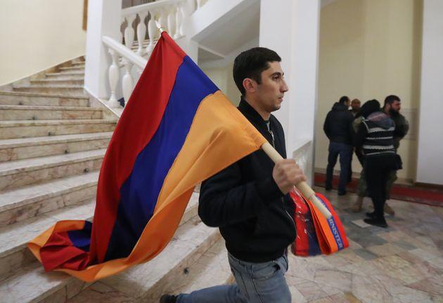 YEREVAN, ARMENIA - NOVEMBER 10, 2020: A man carries an Armenian flag after demonstrators protesting against...