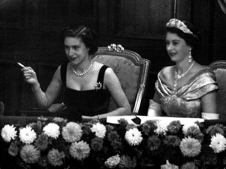 A young Princess Margaret smoking while watching the Royal Variety Performance with her sister, Queen Elizabeth.
