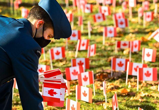 Un militaire dépose des drapeaux canadiens à la veille du jour du souvenir au Sunnybrook Veterans Centre...