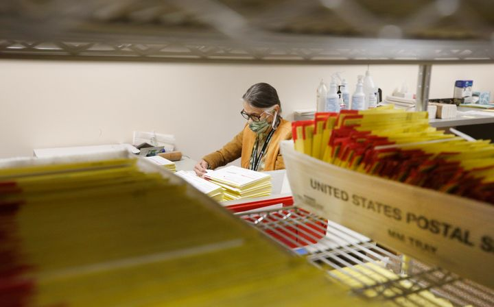 Mail-in ballots in containers from the U.S. Postal Service wait to be processed by election workers in Salt Lake City on Oct.