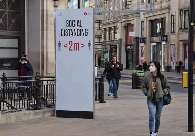 A woman wearing a face mask as a precaution walking past a social distancing sign on Oxford