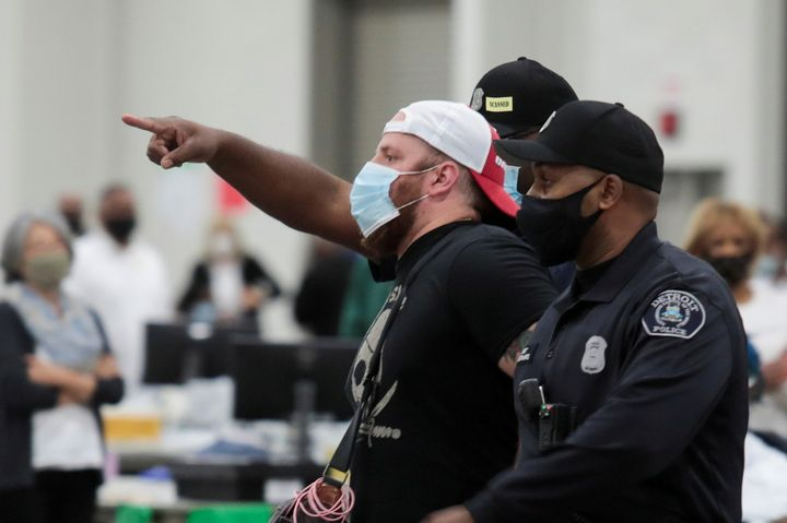 Police escort a poll challenger out after he refused to leave due to room capacity at the TCF Center in Detroit on Nov. 4, 20