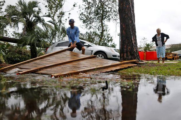 Joseph Howat despeja una cerca dañada por el huracán Michael en su negocio en Panama City Beach,