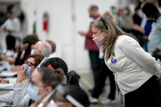 Jacqueline Zaplitny, a Republican election challenger, watches as election inspectors count votes into...