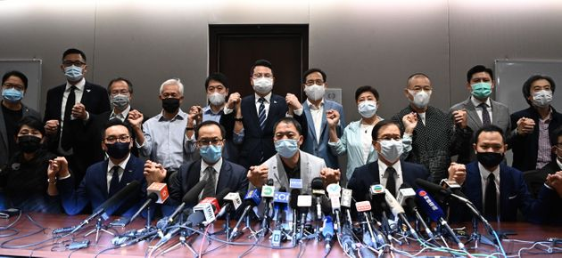 Pro-democracy lawmakers join hands at the start of a press conference in a Legislative Council office...