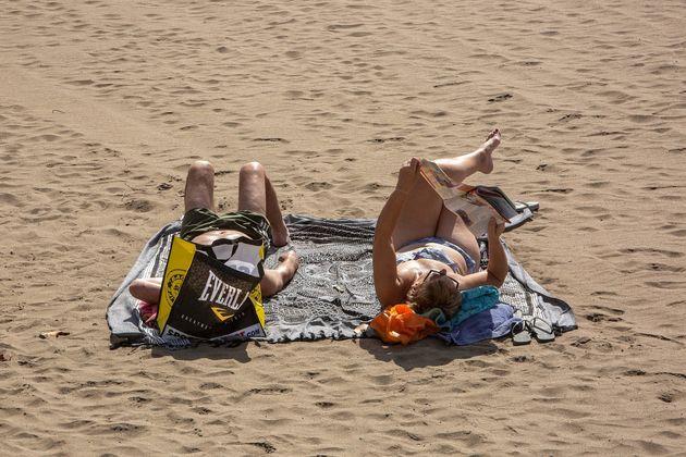 Una pareja toma el sol en playa de Las Vistas, en las islas