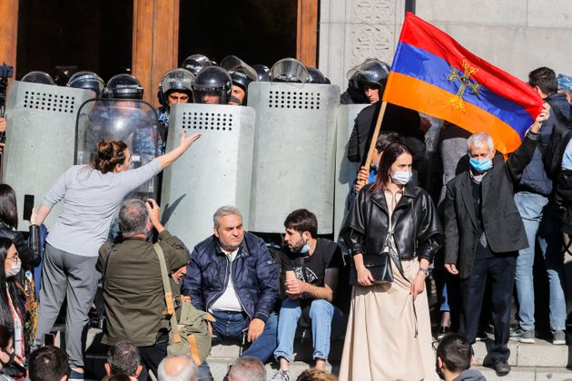 Protesters hold an Armenian national flag during a protest against an agreement to halt fighting over...