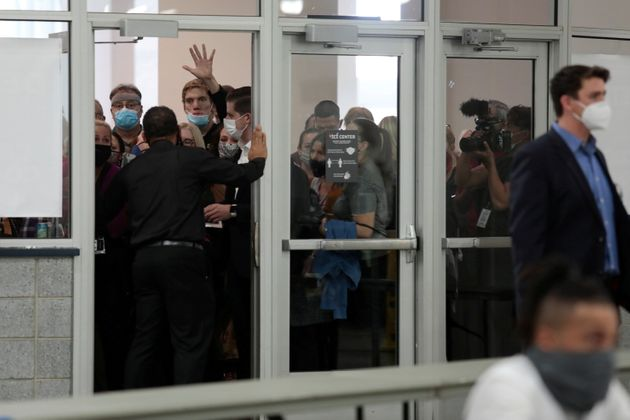 GOP poll challengers react after being asked to leave due to room capacity at the TCF Center in Detroit...