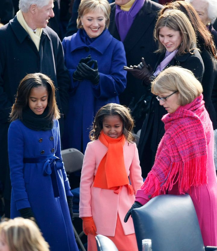 Malia and Sasha Obama pass former President Bill Clinton, then-Sen. Hillary Clinton, and Jenna Bush as they are shown to thei