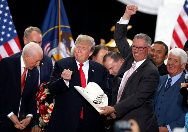 President Donald Trump signs the hat of Bruce Adams, chairman of the San Juan County Commission, after...