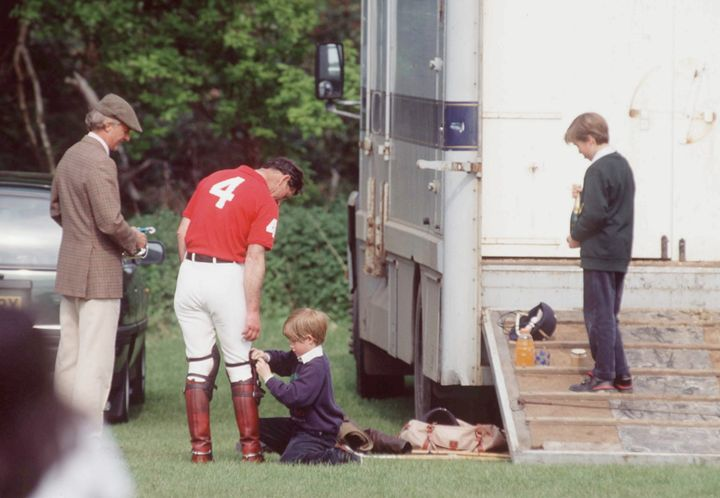 In a candid moment from 1993, a nine-year-old Prince Harry helps his dad with his polo boots.
