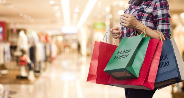 Una mujer lleva unas bolsas de compras realizadas por el Black Friday en un centro comercial.