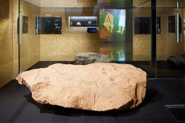 Imagen de la exposición Arte primero. Artistas de la prehistoria; en primer término, bloque...