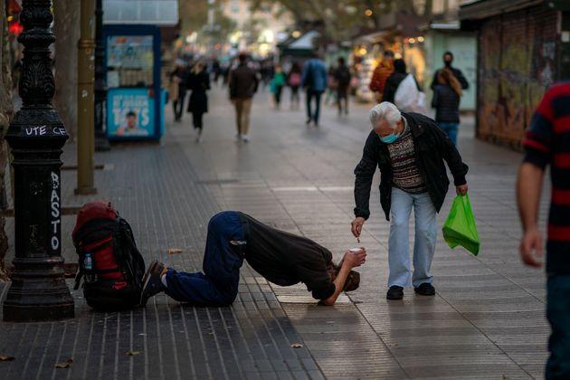 Un hombre dando lismona a otro este jueves en Las Ramblas, Barcelona (AP Photo/Emilio