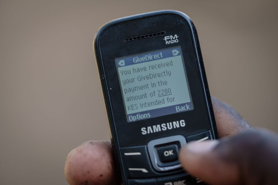 A mobile phone message confirming a universal basic income transaction in the Bondo region of western Kenya. The nonprofit GiveDirectly has been running a UBI program in the area since 2016. Credit:Yasuyoshi Chiba/AFP/Getty Images