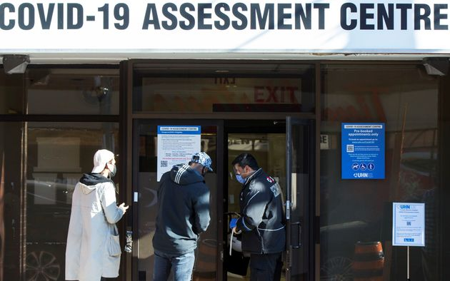 A security officer wearing a face mask and a face shield checks a person's appointment at a COVID-19...