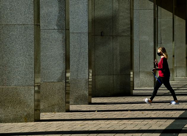 A woman wears a mask as rays of light shine through building columns on a cool sunny fall morning in...