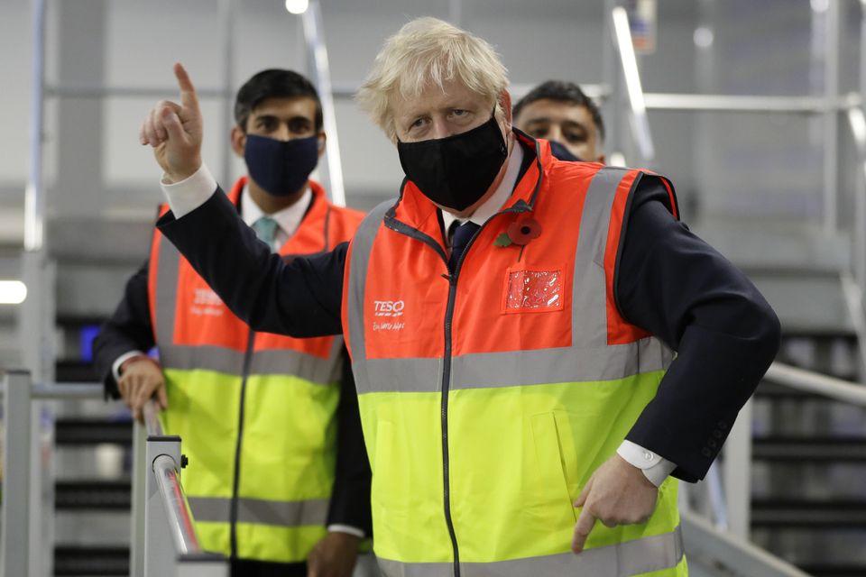 Boris Johnson alongside chancellor Rishi Sunak during a visit to the Tesco Erith distribution centre...