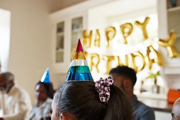 Close-up of girl wearing colorful party hat while celebrating birthday at