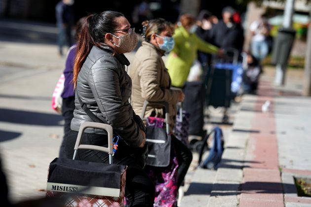 Imagen de archivo de una fila de personas esperando para recibir alimentos de una
