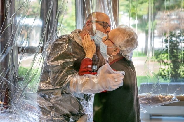 Resident kisses a relative through a plastic sheet installed in a special 'hug room' organised to keep...