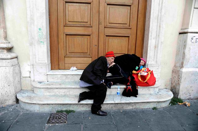 ROMA, ITALY - NOVEMBER 6 : Two homeless people sleep on the steps of the post office building in Piazza...