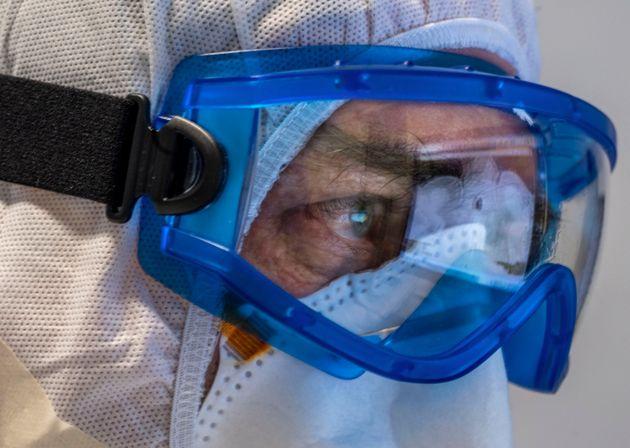 El doctor Giovanni Passeri, con equipo de protección, mira radiografías de los pulmones de sus pacientes...