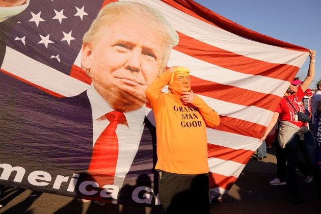 A person in a President Donald Trump mask poses for photos in front of a background with Trump on it...
