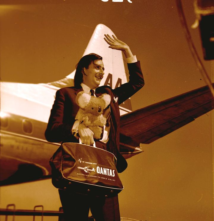 Australian entertainer Barry Humphries holding koala bear and Qantas bag waving on arrival in Melbourne, September 1965.