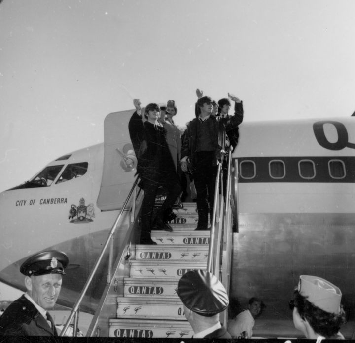 The Beatles wave as they depart on a Qantas flight in 196.