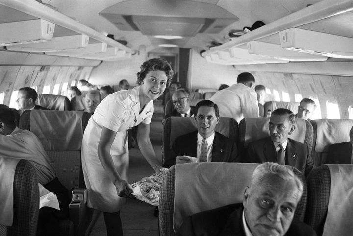 An air stewardess serving food to passengers on board a Qantas Boeing 707 plane at London airport, August 1959.
