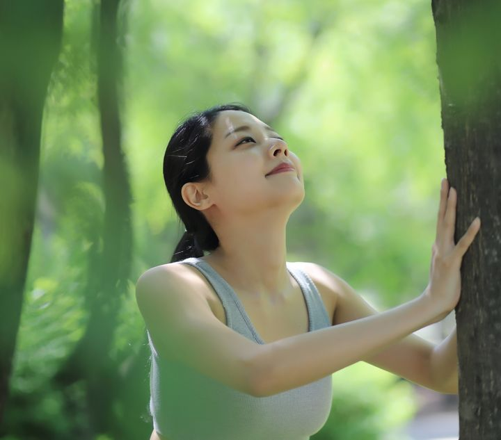 Woman stretching against tree in park