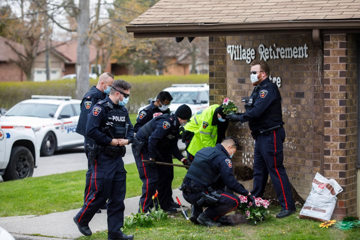 Durham Regional Police plant flowers at the front of Orchard Villa Retirement Centre on Mother's Day, May 10, 2020 in Pickering, Ont.