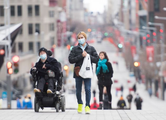 People wear face masks as they make their way along a street in Montreal on Nov. 15,