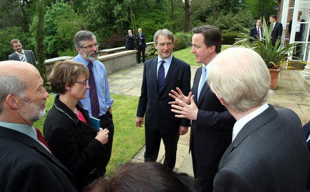 El primer ministro de Reino Unido, David Cameron, conversa con el secretario de estado para Irlanda del...