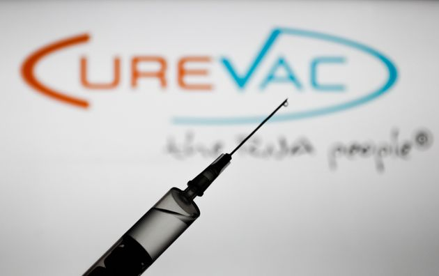 Medical syringe is seen with Curevac company logo displayed on a screen in the background in this illustration...