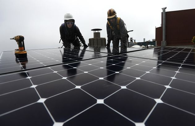 Luminalt solar installers Pam Quan and Walter Morales install solar panels on the roof of a home in San