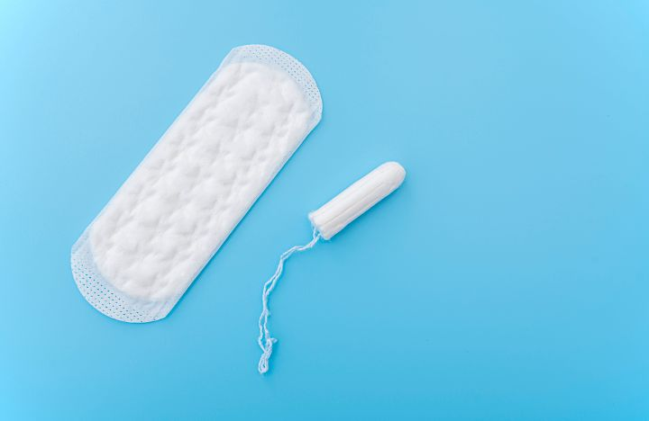 Sanitary napkin and menstruation tampon on blue background, concept picture about women's menstruation cycle, top view