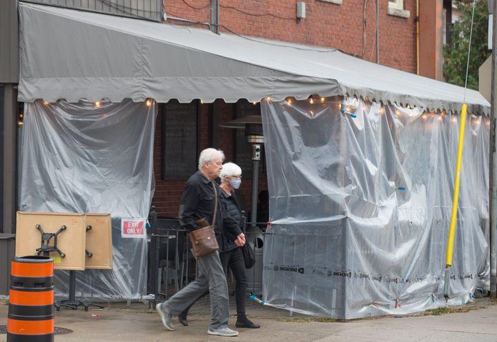 Pedestrians walk by a tented patio on Bloor Street in Toronto.