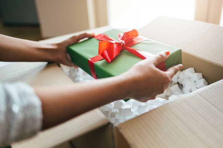 Close up of woman hands opening parcel with present box.