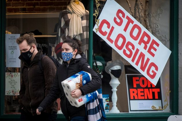 People wears masks as they walk past a store that is closing in Kingston, Ont. on Nov. 16, 2020, as the...