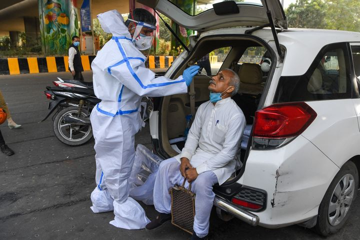 A medical worker collects a nasal swab sample from a man for a Rapid Antigen Test (RAT) for the Covid-19 coronavirus at Delhi-Uttar Pradesh border in Noida on November 18, 2020.