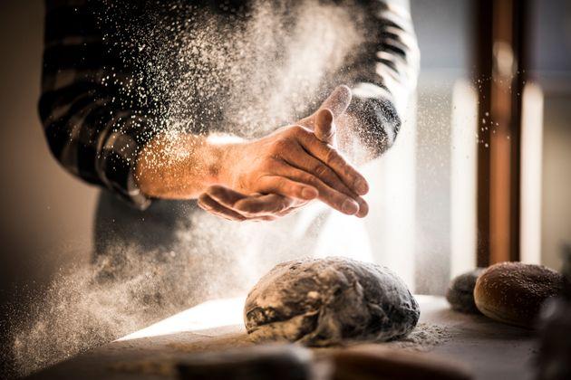 Man preparing black burger buns in kitchen