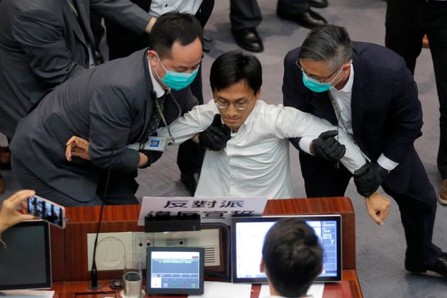 Then pan-democratic legislator Eddie Chu, center, is taken away by security guards during a Legislative...