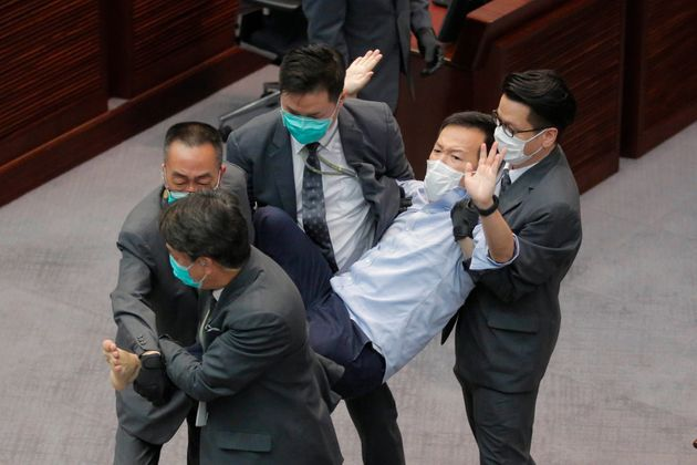 Pan-democratic legislator Raymond Chan Chi-chuen is taken away by security guards during a Legislative...