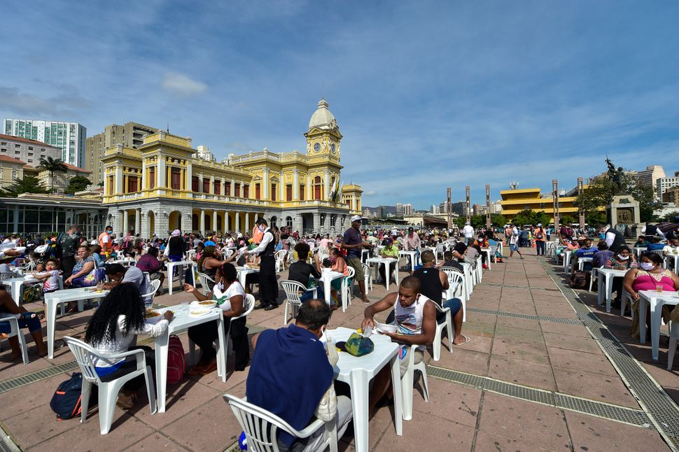 People eat at an open-air restaurant on June 5, 2020, in Belo Horizonte, Brazil. About 3,000 meals are being distributed every Friday, in addition to food, fruit and water. The city has a decades-long policy of guaranteeing residents affordable, healthy food. Credit: Pedro Vilela/Getty Images
