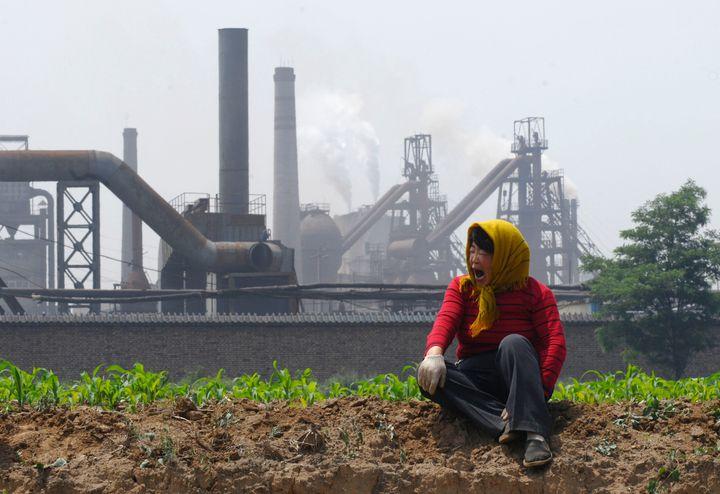 Dans le secteur de l'énergie, les émissions de CO2 ont baissé, une bonne nouvelle mais l'amélioration risque d'être temporaire, selon Climate Transparency. Image d'illustration: une agricultrice devant une cokerie à Changz, en Chine.