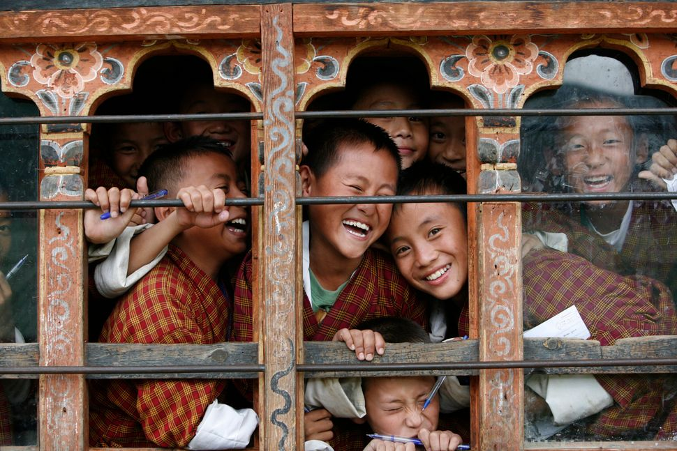 Schoolchildren react to the camera through the window of their classroom in a school in Thimphu, Bhutan, in 2010. Credit: Reuters