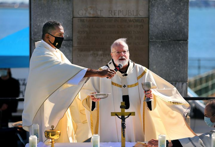 Rev. Oscar Pratt, left, holds the microphone as Cardinal Sean O'Malley speaks during a Mass for Racial Healing in South Bosto